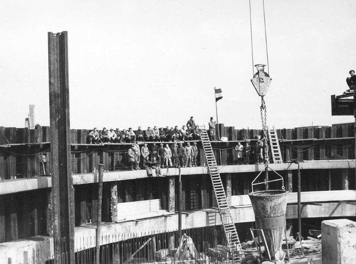 De aanleg van de keersluis in Zierikzee, met arbeiders op de rand terwijl er beton wordt gestort.