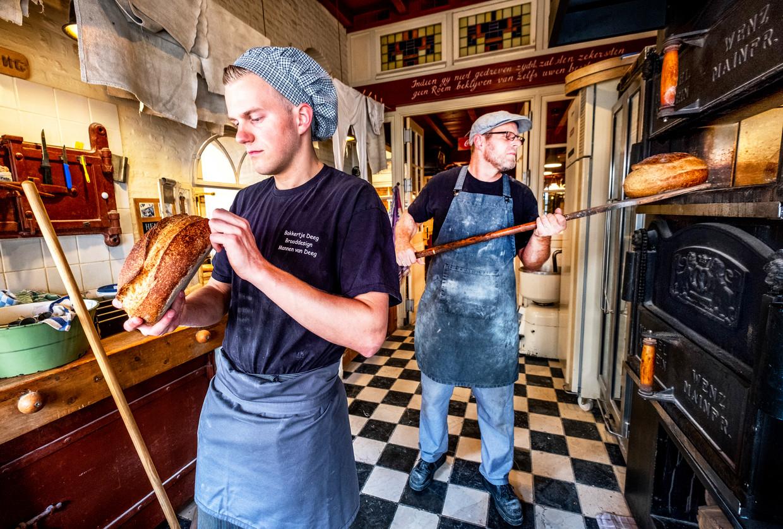 Bakker Lucas Vermeulen (rechts) en zijn zoon en opvolger Giel Vermeulen aan het werk in hun bakkerij in Heusden.  Beeld Raymond Rutting