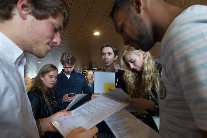 Geslaagde vwo-leerlingen van het Gerrit Komrij College in Winterswijk bekijken tevreden hun cijferlijsten.