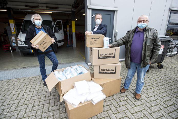 FC Twente fanclub Hardcore Eibergen biedt voedselbank Oost Achterhoek 10.000 mondkapjes aan, zodat minima ook beschermd zijn tegen corona. Vlnr. Henk Kok (voorzitter Voedselbank Oost Achterhoek) , Jordy Geerdink (importeur persoonlijke beschermingsmiddelen) en Heinz Clasen (bestuurslid voedselbank).