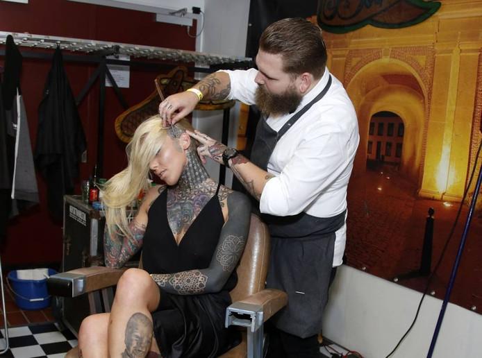 Het Engelse tattoomodel Lauren de Brock wordt geschoren door Hulster barbier Kjeld Van Riemsdijk.
