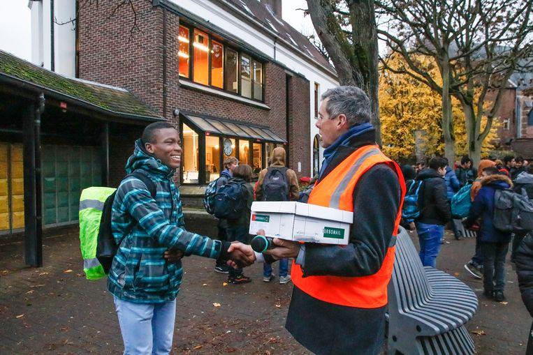 Directeur van de eerste graad van de Technische Scholen Mechelen Marc Steemans bedankt een leerling, omdat hij goed zichtbaar is in het verkeer.