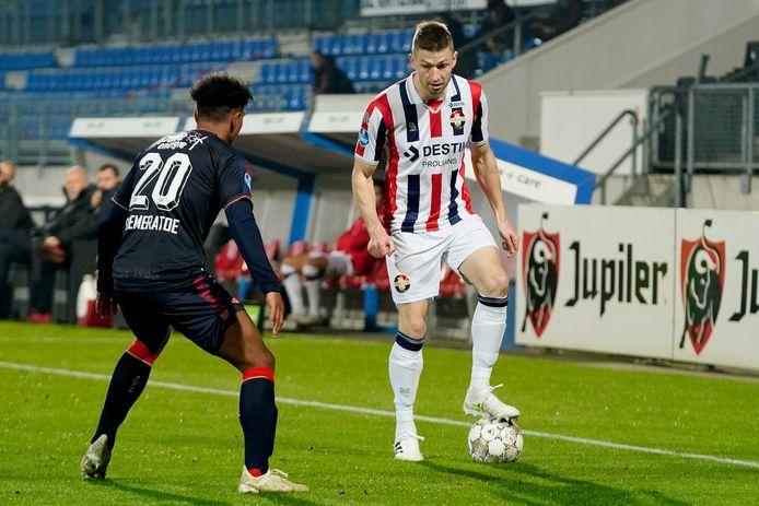 Jan-Arie van der Heijden (rechts) wacht af wat FC Twente-speler Godfried Roemeratoe gaat doen.