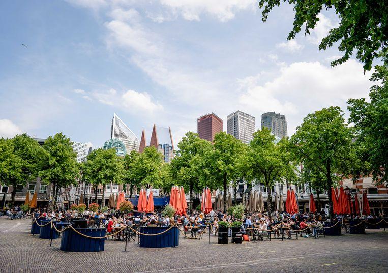 De terrassen zijn weer open, hoewel nog niet iedereen durft. Op de achtergrond: ministeries in Den Haag.  Beeld ANP