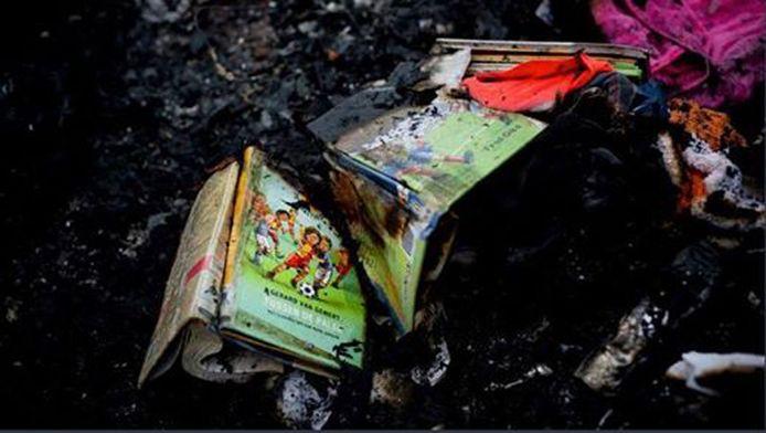 Het kinderboek van schrijver Gerard van Gemert tussen het puin van het gecrashte vliegtuig.