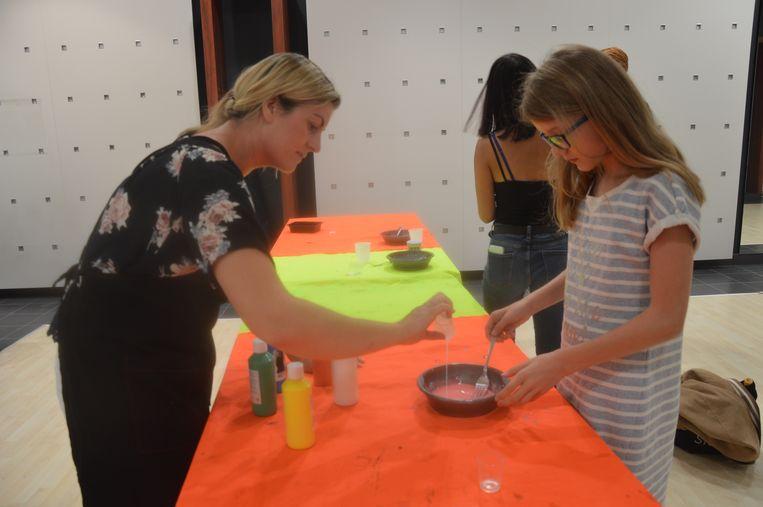 De deelnemers krijgen uitleg over hoe ze het slijm maken.