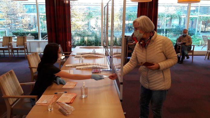 De Moergestelse Riky Martens meldt zich mét mondkapje bij het stembureau van Park Stanislaus, dat van spatschermen is voorzien