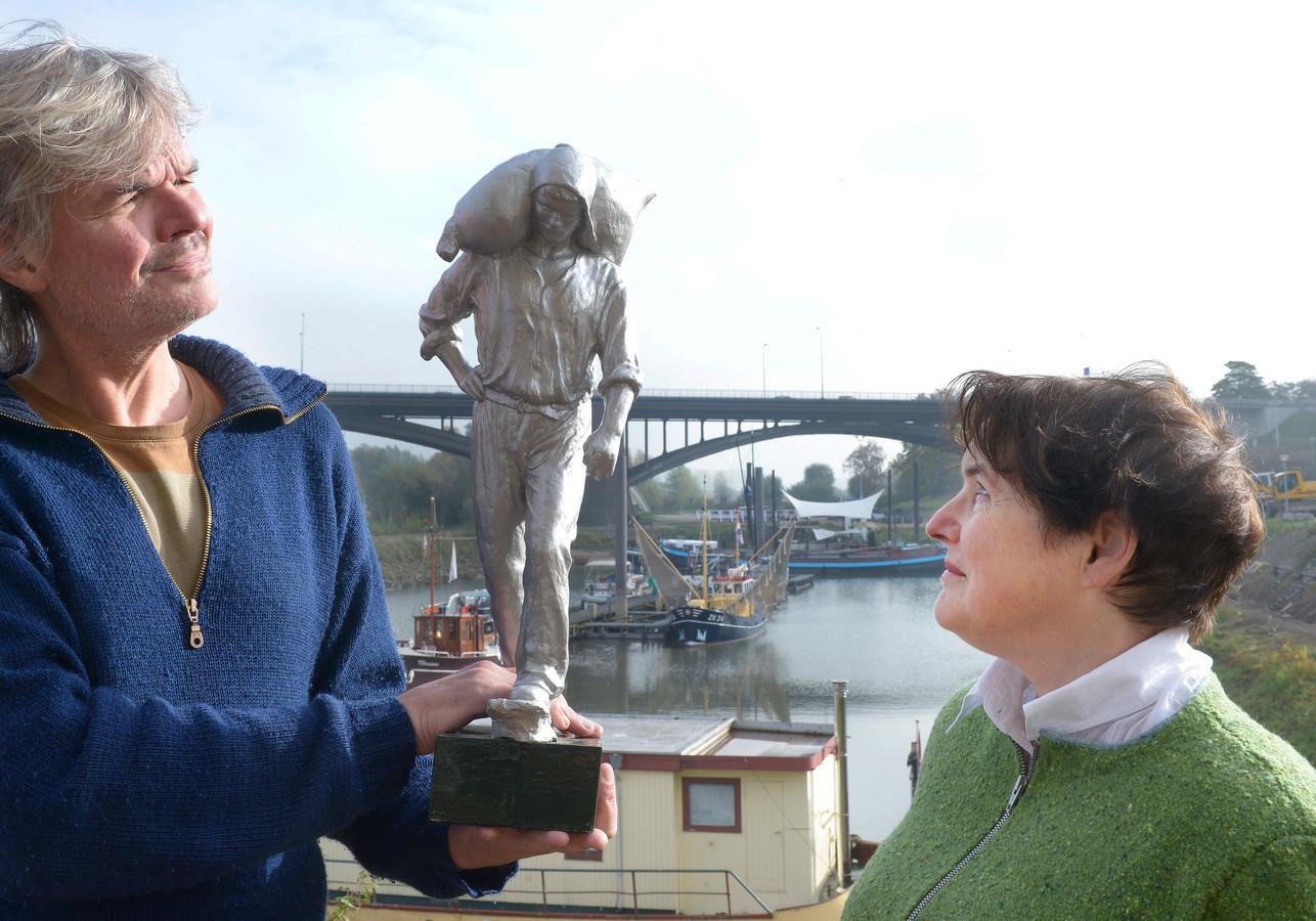 Kunstenares Margriet Hovens en model Frank Antonie van Alphen bij de Lindenberghaven met een miniatuur van het standbeeld De Kaaisjouwer. Voor de winnaar van de Kaaisjouwer Run ligt staat een replica van het beeld klaar.