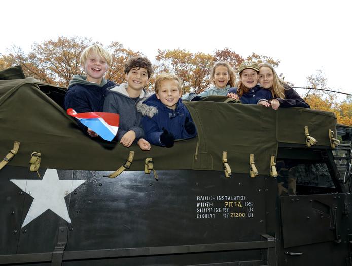 Kinderen rijden mee tijdens de herdenking in Gemond