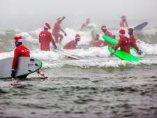 Surfende kerstmannen aan strand Scheveningen