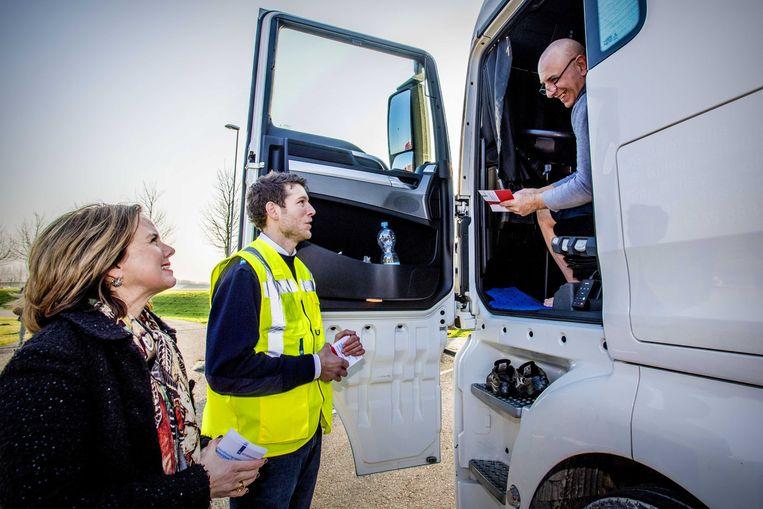 Minister Cora van Nieuwenhuizen deelt folders uit aan vrachtwagenchauffeurs om ze te informeren over de nieuwe regels dat het rusten op parkeerplaatsen op zondag niet meer is toegestaan.  Beeld ANP