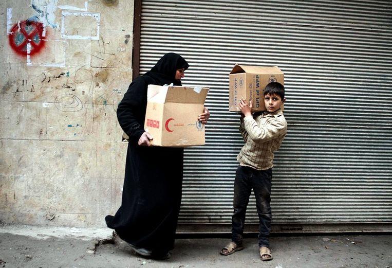 Een man en een vrouw dragen dozen met voedsel in Damascus op archiefbeeld. Beeld epa