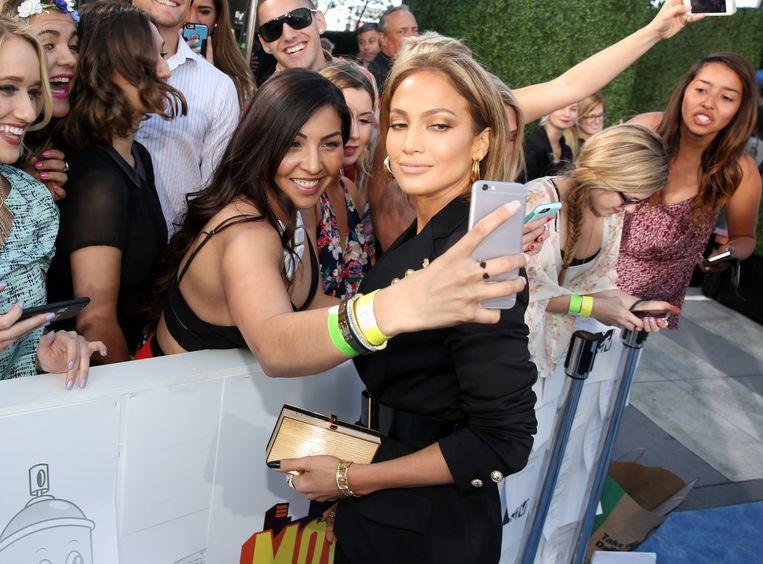 Jennifer Lopez poseert voor een selfie van een fan. Beeld ap