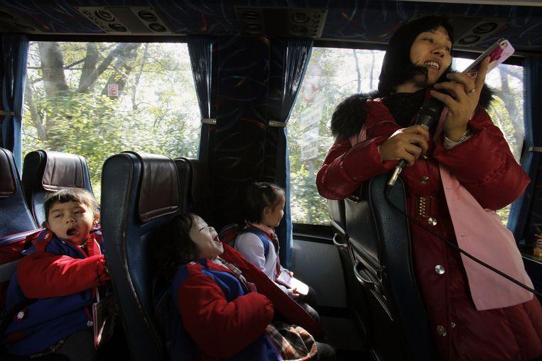 Met de ene bus gaan de kinderen tot de grens, in Hongkong stappen ze weer in de andere bus. Beeld reuters