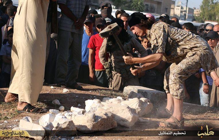 Een IS-strijder verbrijzelt oude kunstschatten uit Palmyra. Beeld afp