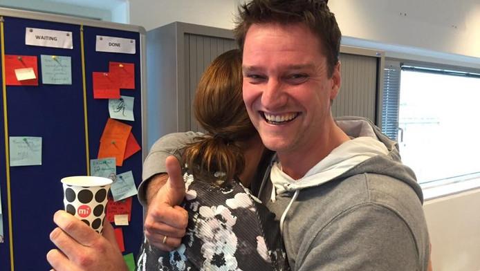 Klantenservicemedewerker Nicole krijgt een knuffel van haar collega Erik.