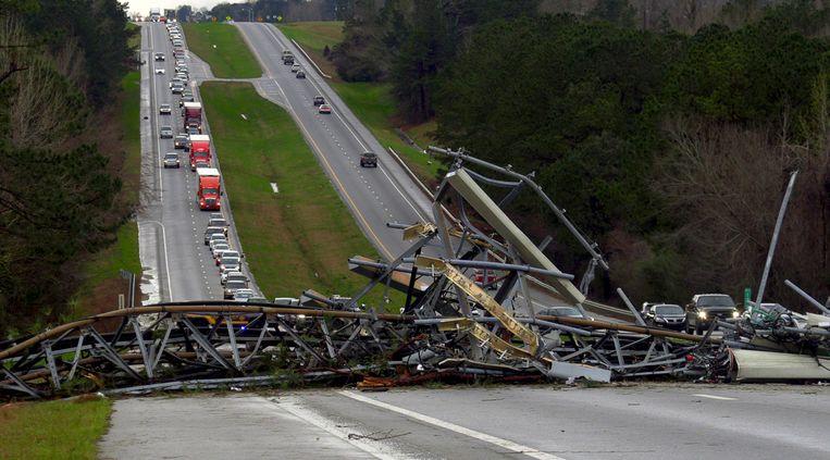 Een telefoonmast is door een tornado omgevallen en ligt over de weg in Alabama.  Beeld AP