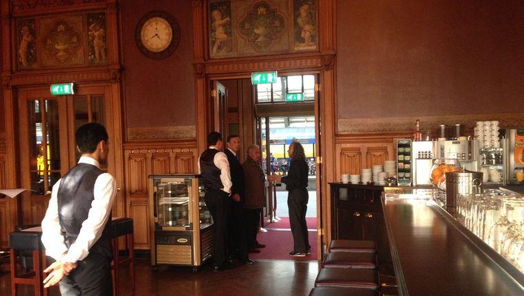 Mario Brandt, in bruin jasje, voert een gesprek met de voorzitter van het stembureau Beeld Het Parool