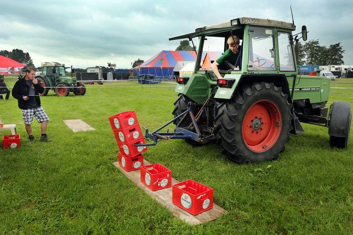 Een deelnemer aan een trekkerbehendigheidswedstrijd in Gilze stapelt kratjes Dommelsch. Hoewel de brouwerij in Dommelen ook voor stikstof in de natuur zorgt, heeft het bedrijf nog altijd geen natuurvergunning.