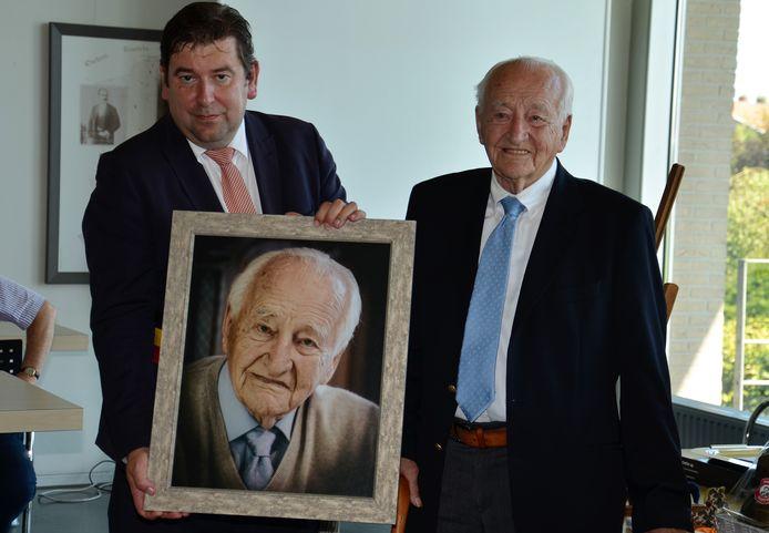 Burgemeester Bart Dochy overhandigt een portret aan de 100-jarige Gerard Berteloot.