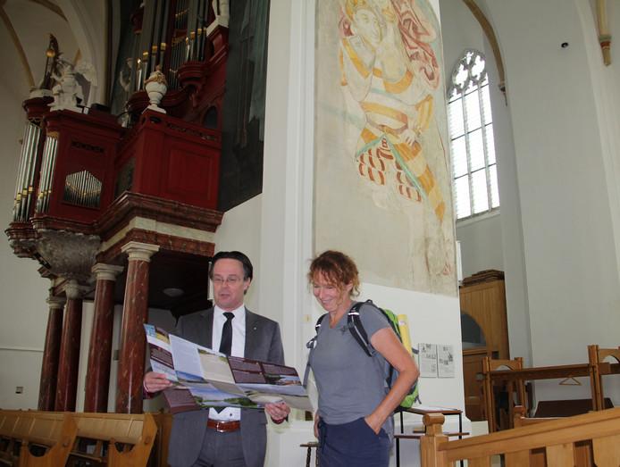 'Wandelvrouw' Bregje Schipper en burgemeester Eddy Bilder bij de afbeelding van Christoffel in de Grote Kerk van Hasselt.
