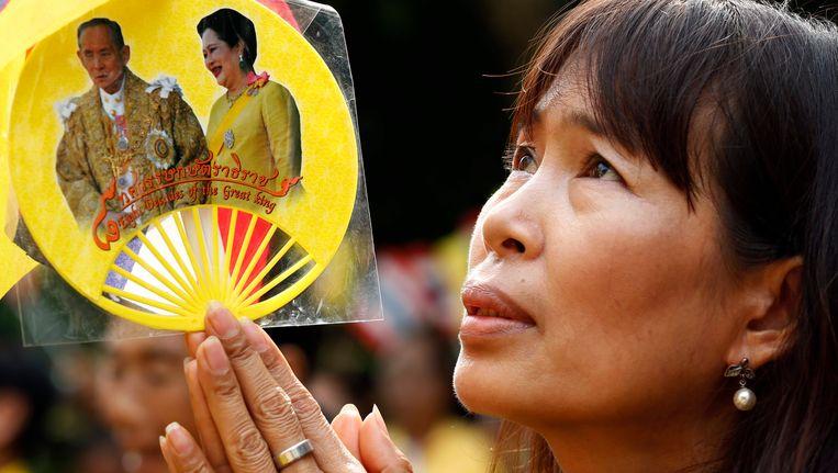 Een Thaise vrouw betuigt haar steun aan de koning tijdens zijn 87ste verjaardag. Beeld epa