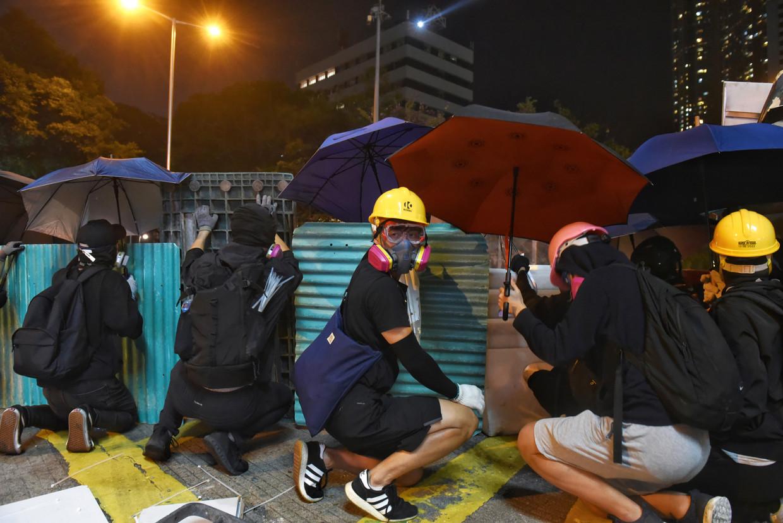 Betogers in Hongkong verschuilen zich achter barricades, gasmaskers en paraplu's in een confrontatie met de oproerpolitie.