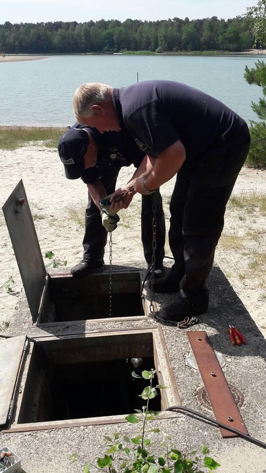 Bij recreatieplas 't Zand in Alphen plaatsen Marc van den Broek en Gerrie van Riel een tweede pomp geplaatst om meer zuurstof in het water te krijgen.