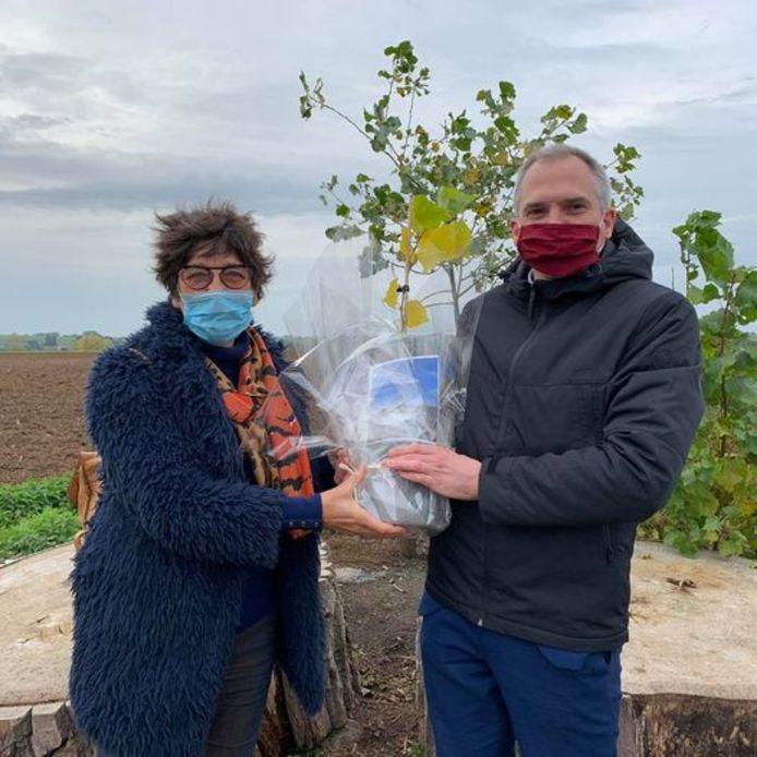 Gedeputeerde Annemie Charlier overhandigt het eerste stekje van de Vollanderboom aan Vlaams minister voor Onroerend Erfgoed Matthias Diependaele.