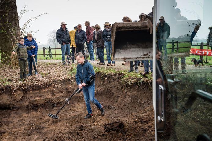 Tim Hummelink uit Goor stapt in een gegraven gat om met een metaaldetector te zoeken.