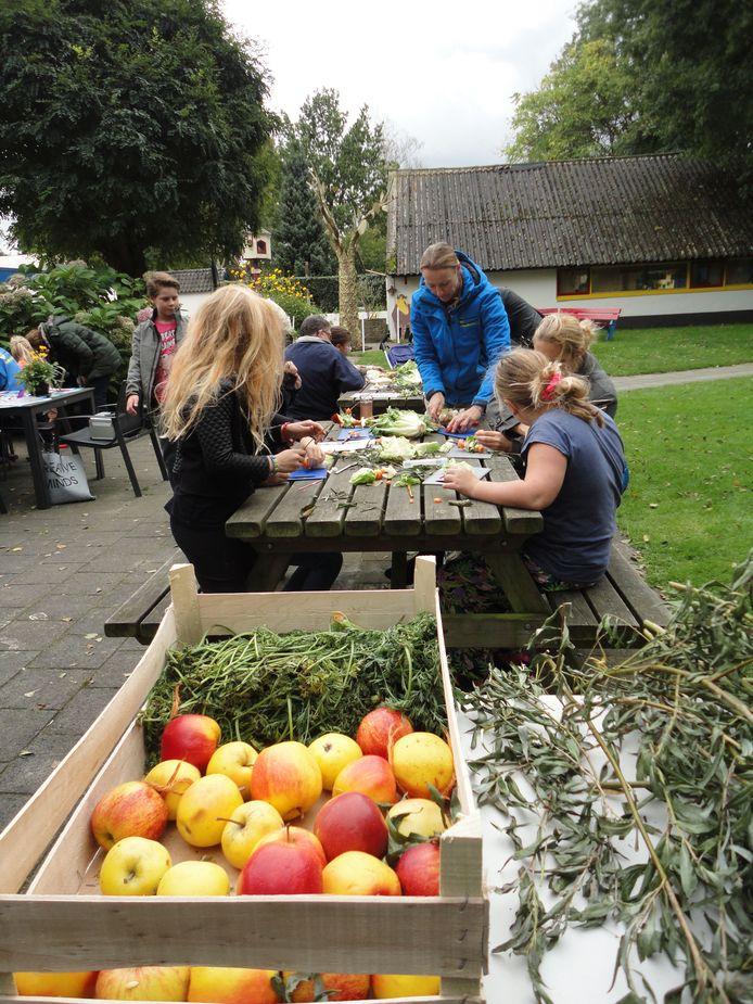 Kinderen maken op de kinderboerderij De Veenweide in Soest een dierentraktatie van wilgentakken, groente en fruit.