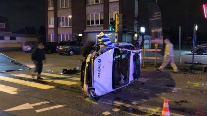 Politiewagen over de kop na botsing met auto