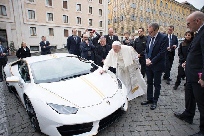 Paus Franciscus zet zijn handtekening op de bolide.