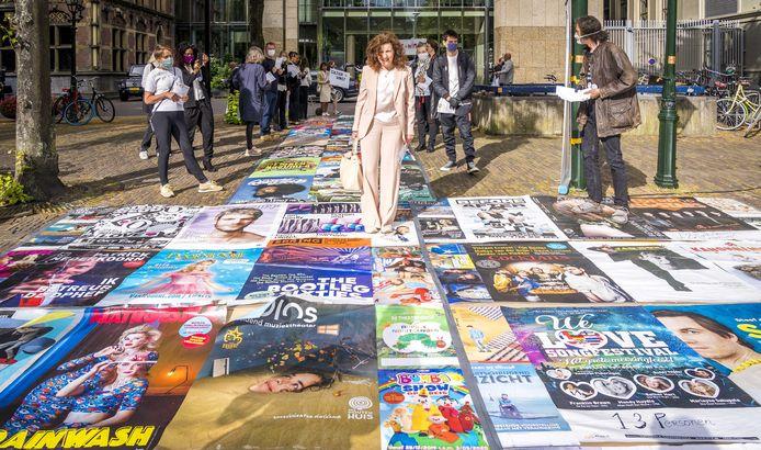 Minister Ingrid van Engelshoven (Cultuur) loopt over een loper, gemaakt van posters van alle voorstellingen en concerten die vanwege het coronavirus werden geannuleerd.