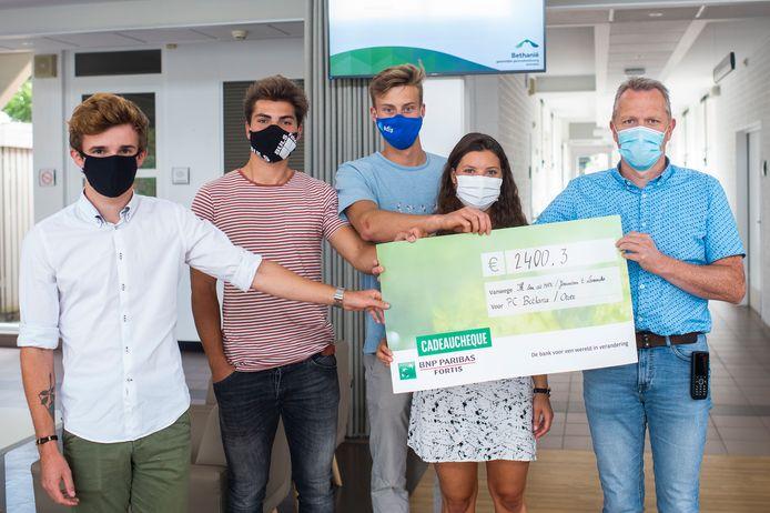 Maxime Hermans (links) overhandigt de cheque van 2.400,3 euro aan Johan Goetschalckx van afdeling Oever (rechts). In het midden staan de vrienden van Maxime die de jeneverbar organiseerden ten voordele van vzw 'Ik ben de Max!'