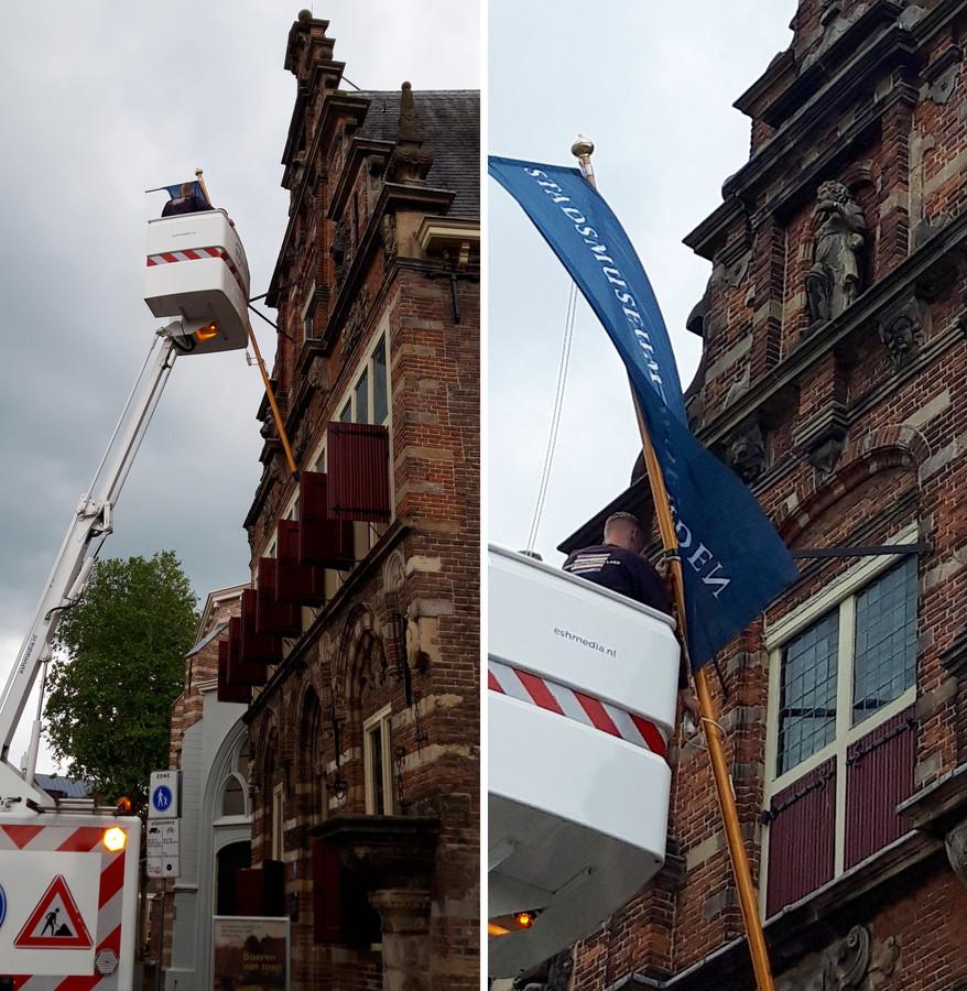 De banier wordt alsnog aan de vlaggenmast van het Stadsmuseum Woerden bevestigd.