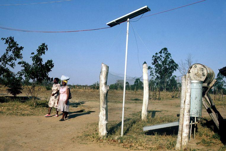 Een zonnepaneel met een hekje eromheen, ergens in Zimbabwe. Schone energie is een voorbeeld van een concrete oplossing voor luchtvervuiling. Beeld Roel Burgler/Hollandse Hoogte