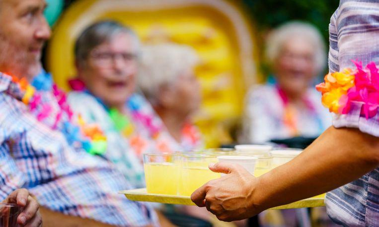 Bewoners van een Rotterdamse woonzorglocatie krijgen een koud drankje voor aanvang van een concert van een brassband. Beeld ANP