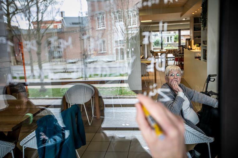 Jee Kast schrijft een gedicht in spiegelschrift op het raam van rusthuis Orelia.