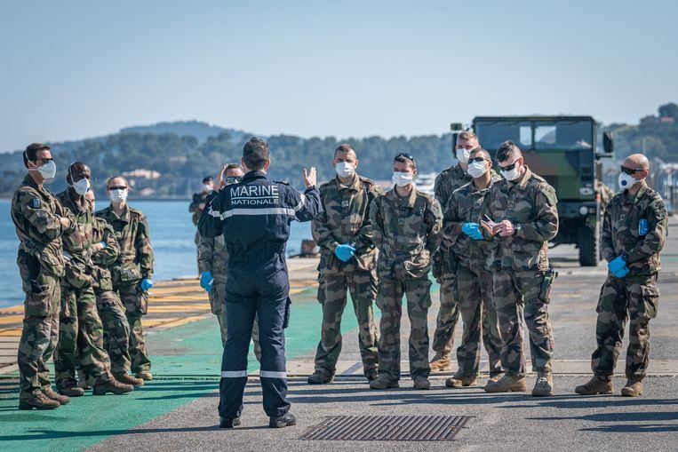 Briefing van het personeel dat het Franse vliegdekschip Charles de Gaulle gaat desinfecteren. Beeld EPA