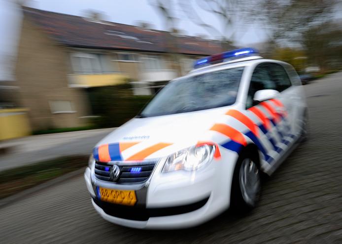 Een politiewagen rukt met zwaailichten uit.