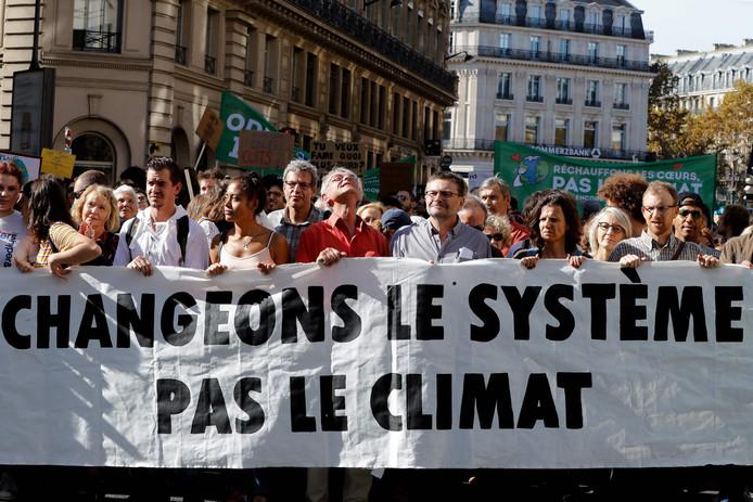 Betogers lopen met een spandoek met de tekst: verander het systeem, niet het klimaat.