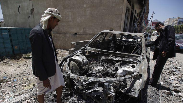 Inwoners van Sanaa maken de schade op na een bombardement van Saoedische vliegtuigen. Beeld ap