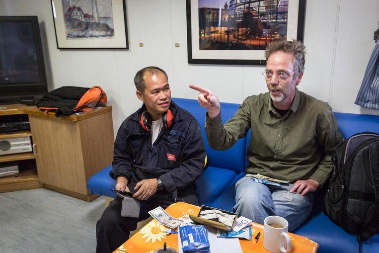 Havendominee Leon Rasser (r) verkoopt simkaarten aan zeelieden Beeld Dingena Mol