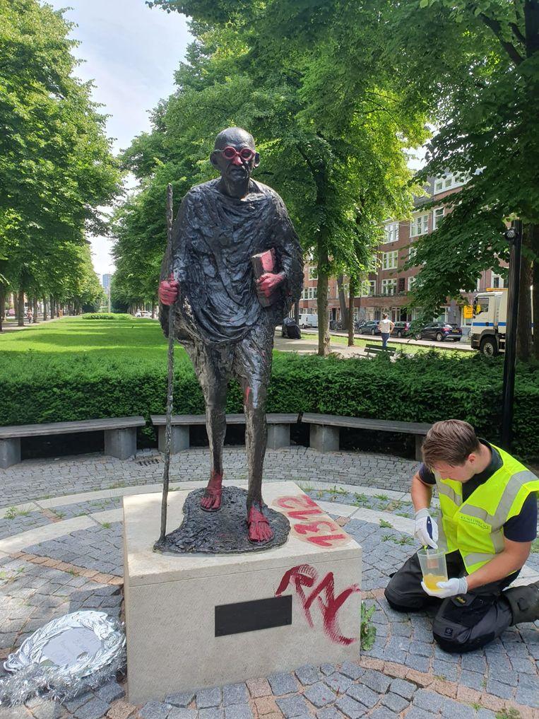 Een medewerker van de Kunstwacht maakt het beeld schoon. Beeld Olaf Heyblom