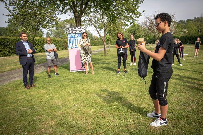 Gedeputeerden Jo-Annes de Bat (l) en Anita Pijpelink (midden) reikten onlangs tijdens een (buiten)dansles van dansschool Body Action Goes de eerste Sport & Cultuur TAS voor THUIS uit aan intermediairs en sport- en cultuurorganisaties. Jakysh van Beelen kreeg het eerste tasje om uit te pakken. In de rugzakjes zitten ook de aanvraagformulieren voor een bijdrage voor contributie van sport- en cultuurverenigingen.