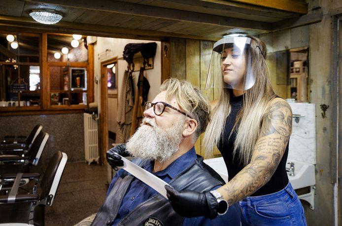 Kapper Ronald Verhulst zit in de stoel en krijgt een mondkapje om. De kapster draagt een masker.
