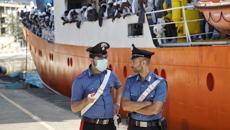 Twee politie-agenten houden de wacht als de Aquarians is aangemeerd aan de kade van Messina, op het eiland Sicilië. Beeld Bram Janssen/AP