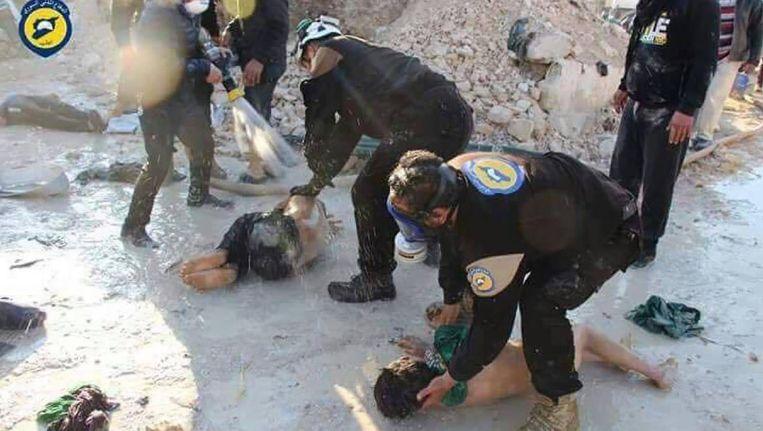 Reddingswerkers van White Helmets besproeien slachtoffers van de gifgasaanval in Khan Sheikhoun dinsdag met water. Beeld White Helmets Twitter)