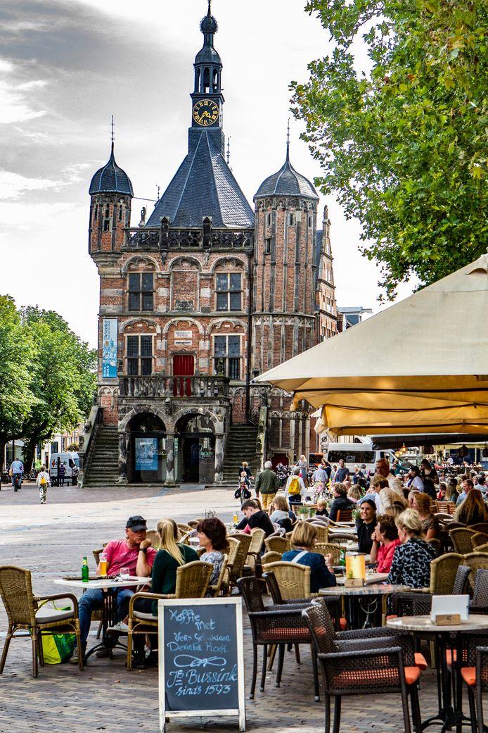 De horeca op de Deventer Brink in betere tijden, met volle terrassen. Als de coronacrisis achter de rug is. mogen de terrassen op de pleinen in de stad een uurtje langer open blijven (tot 02 uur).